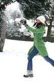Beautiful woman in winter setting. Beautiful young woman in green coat and hat in throwing snow Stock Photos