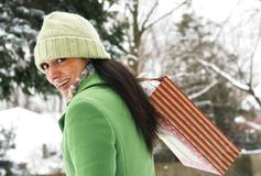 Beautiful woman in winter setting. Beautiful young woman in green coat and hat in carrying package Royalty Free Stock Images