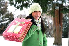 Beautiful woman in winter setting. Beautiful young woman in green coat and hat in carrying package Royalty Free Stock Photos