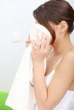 Beautiful woman wipes her face with a towel Stock Image