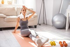 Beautiful woman wiping sweat off forehead after workout. Well-deserved break. Pleasant young woman sitting on the yoga mat and wiping sweat off her forehead royalty free stock photography