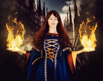Beautiful woman witch in fantasy medieval dress. Fire magic. Beautiful woman witch in fantasy medieval dress and long hair. Eyes closed. And hands are divorced Stock Photo