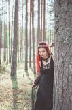 Beautiful woman witch with red hair in the forest stock photography