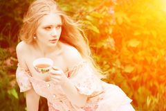 Beautiful Woman With Flowering Tree Drinking Tea In Sunset In Sp Stock Photography