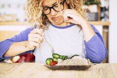 Free Beautiful Woman With Glasses Looking With Disgust Some Vegetables And Rise On The Table - She Is Going To Eat Healthy To Feel Stock Photo - 191685120