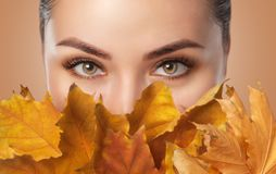 Free Beautiful Woman With Long Eyelashes And With Beautiful Smokey Eyes Makeup Holds Yellow Leaves Near The Face. Eyes Close Up. Stock Photography - 160929372
