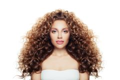 Beautiful Woman With Long Healthy Curly Hair Isolated On White. Wavy Hairstyle, Natural Makeup, Young Female Model Face Stock Photo