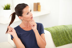 Beautiful woman wondering while sitting at home Stock Images