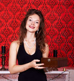 Beautiful woman with wooden box smiling in red vintage interior Stock Photography