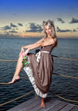Beautiful woman  on a wooden platform over  the sea during a sunset Royalty Free Stock Photography