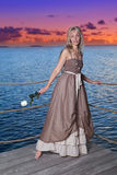 The beautiful woman on a wooden scaffold over the sea during a sunset Stock Photo