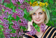 Beautiful woman wore a wreath of flowers. A beautiful woman  On his head a crown of flowers  lilac bush Beautiful woman wore a wreath of flowers Royalty Free Stock Photography
