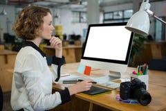 Beautiful woman working on desktop pc. Side view of a beautiful woman working on desktop pc in creative office Stock Image