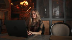 Beautiful woman working on her laptop on a stylish urban restaurant.  stock video