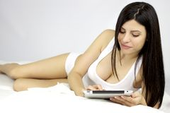 Beautiful woman working with ipad in bed Royalty Free Stock Photos