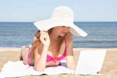 Beautiful woman working on laptop at the beach Stock Photography