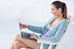 Beautiful woman working on laptop computer on her knees Royalty Free Stock Image