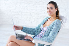Beautiful woman working on laptop computer on her knees Stock Photography