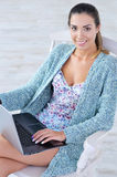 Beautiful woman working on laptop computer on her knees Royalty Free Stock Photo