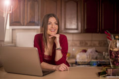 Beautiful woman working on laptop in the kitchen Stock Image