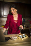 Beautiful woman working on laptop in the kitchen Stock Photography