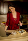 Beautiful woman working on laptop in the kitchen Royalty Free Stock Photo