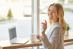 Beautiful woman working on laptop near the window and call a waiter, raising her arm at the cafe. Beautiful young woman working on laptop near the window and Royalty Free Stock Images