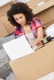 Beautiful woman working with laptop during office relocation Stock Photos