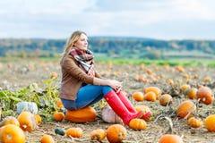 Beautiful woman working on pumpkin field Royalty Free Stock Photo
