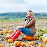 Beautiful woman working on pumpkin field Royalty Free Stock Photo