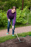 Beautiful woman working with rake on garden bed Stock Photo