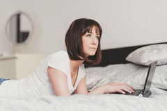 Beautiful woman works on laptop in bedroom Stock Photos