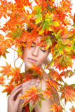 Beautiful woman wrapped in autumn leafs Stock Photos