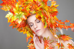 Beautiful woman wrapped in autumn leafs Royalty Free Stock Photo