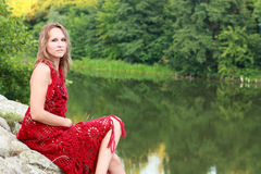 Beautiful woman wrapped a red shawl on the river Royalty Free Stock Photography