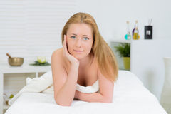 Beautiful woman wrapped in a towel laying in spa Stock Photography