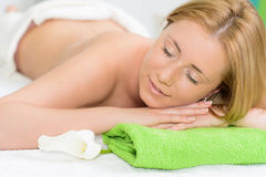 Beautiful woman wrapped in a towel laying in spa Royalty Free Stock Images