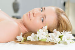 Beautiful woman wrapped in a towel laying in spa with white flow Royalty Free Stock Image