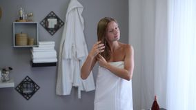 Beautiful woman wrapped in towel after shower is applying coconut oil her wet hair. Hair care concept. Beautiful woman wrapped in towel after shower is applying stock footage