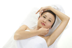 Beautiful woman wrapped in towels. A beautiful Asian womam lying on a towel covered surface Stock Photos