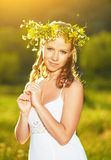 Beautiful woman in wreath of flowers  in the green grass outdoor Stock Photos