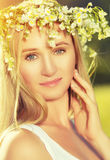 Beautiful woman in wreath of flowers lies in the green grass out Stock Photo