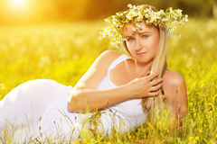 Beautiful woman in wreath of flowers lies in the green grass out Royalty Free Stock Photos