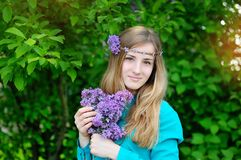 Beautiful woman with a wreath of lilac color walks in the park Stock Images