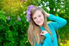 Beautiful woman with a wreath of lilac color walks in the park Stock Photos