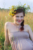 Beautiful woman in wreath smiles in yellow field at sum Stock Photo