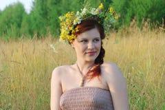 Beautiful woman in wreath of wild flowers in dry field Stock Photo