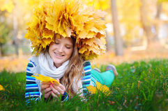 Beautiful woman in a wreath of yellow leaves lying on the grass Stock Images