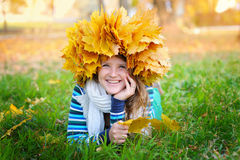 Beautiful woman in a wreath of yellow leaves lying on the grass Royalty Free Stock Images