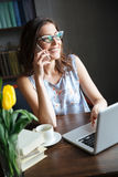 Beautiful woman writer sitting indoors while talking by phone Royalty Free Stock Image